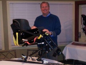 Bancroft founder Paul Jenkins poses with specialty skiing equipment for disabled veterans.